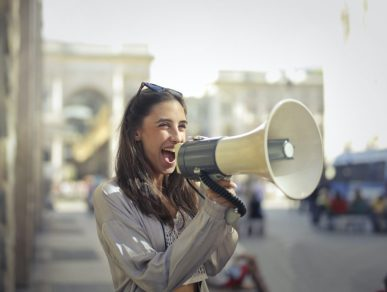 Image of person with a mega phone making noise, representing the early pioneers of the breast cancer movement using their voice to increase breast cancer awareness.