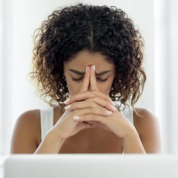 Image of person with hands in front of their face, looking exhausted as they try to work at the computer.