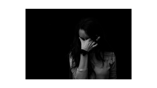 Image of woman holding her head in her hands. The mood is somber and image is black and white, representing the fear and anxiety and isolation that comes with a Lichen Sclerosus diagnosis.