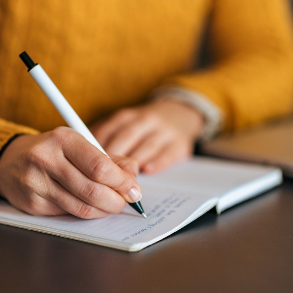 Image of person writing in a notebook representing me writing down content for the blog.