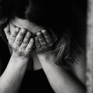 Black and white image of person covering their face in shame. This represents how I felt the first time after checking my vulva.