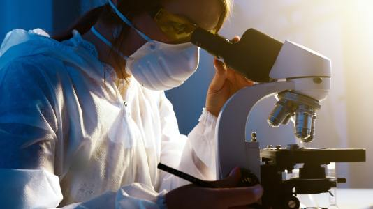 Image of a technician looking into a microscope analyzing test results. When you see a nutrition therapist they may run tests to help determine what is out of balance in your body.