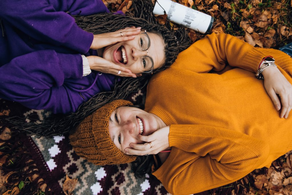 Image of two friends lying on the ground outside, laughing. This represents how Louise moved from denial to acceptance by starting to open up to friends and family about her LS.