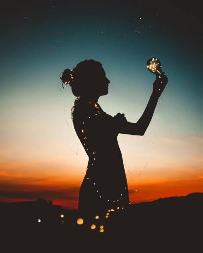 Image of a silhouette of a person in the evening. Their body is lite up by fairy lights and they hold a light in their hands. This represents the light and hope for a future full of Lichen Sclerosus awareness and research.