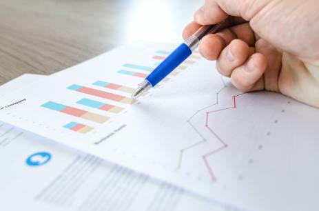 Image of a person holding a pen while analyzing data, representing the topic of research and Lichen Sclerosus.