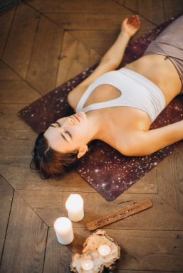 Image of a person lying down on a yoga mat, meditating. This is similar to the post I take when using dilators, except my head is usually more propped up.