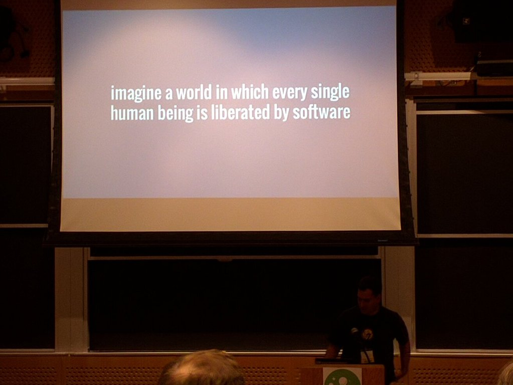 """Speaker in a classroom in front of a slide. The slide is plain text and reads """"imagine a world in which every single human being is liberated by software"""""""