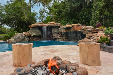 Sitting by the poolside fire pit with two log seats and a view of the backyard pool waterfall