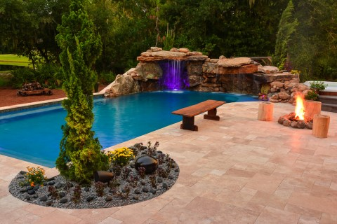 Full view of the natural rock lagoon pool, complete with outdoor sound system, fire pit and seating areas