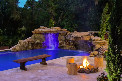 A natural wood bench sits by the edge of this real rock lagoon waterfall with a fire pit