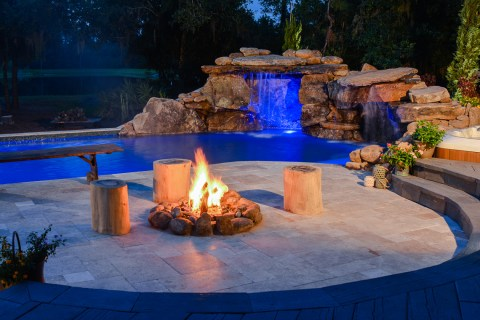 A blazing fire pit warms the evening air in a large outdoor living area complete with natural stone lagoon pool