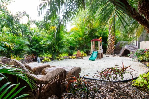 Hidden play area and seating in tropical landscaping