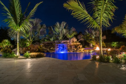 Natural lagoon pool at night with fire pits and stone grotto