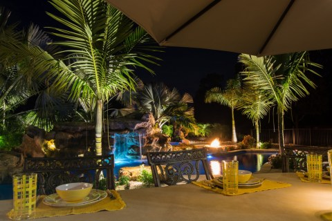 Rock waterfall Pool Outdoor Kitchen and Bar natural lagoon pool at night