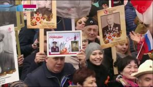 crowd of people holding portraits of veterans
