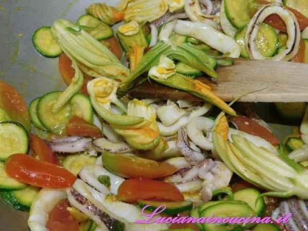 Ed i fiori di zucchina puliti e divisi in 3 o 4 parti.