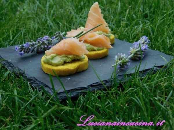 Disporre su ogni crostino una rosetta di salmone affumicato ed un pezzo di stelo di erba cipollina.