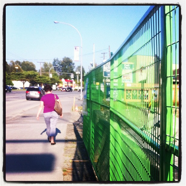 Walking by a green fence