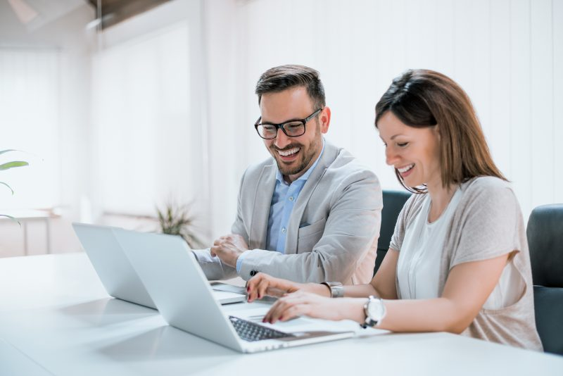 Two people sitting together working in an office