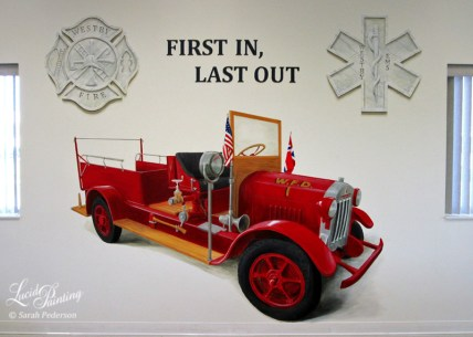 """Antique red fire engine is painted between two windows with emblems above it and the phrase, """"First in, Last out"""" in the center. The engine has the United States Flag and the Norwegian Flag on either side of the windshield."""