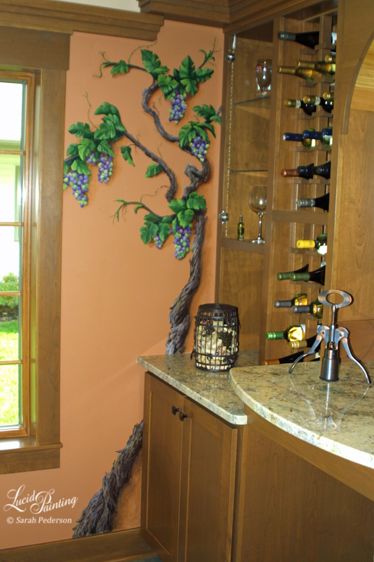 A trompe l'oeil vine with purple and green grapes. The vine is heavily textured with peeling bark and extends partially behind the countertop as it makes its way up toward the ceiling. Delicate tendrils climb along the wall.