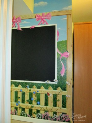 This summer landscape surrounds a chalkboard. Alyssum, daisies, and morning glories weave in and out of the wooden fence, and shiny pink ribbon appears to hold the chalkboard onto the support beam. Butterflies and fairies complete the scene, along with a hummingbird, caterpillar, and ladybugs.
