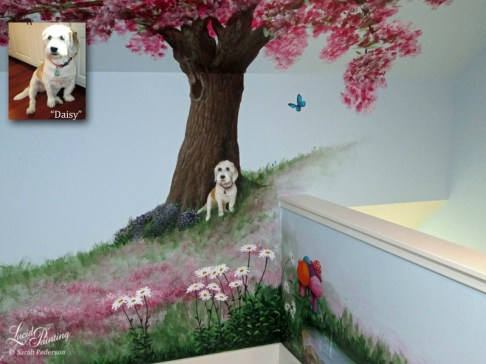 A small pet dog lounges in front of a blooming cherry or apple tree in a meadow of pink flowers. Daisies grow up near the baseboard trim, and a blue butterfly is heading her way. Purple flowers surround the roots of the tree.