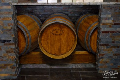 Three life-sized wine barrels are painted in perspective on a flat wall under a countertop. The middle barrel features my client's name, and appears to be branded into the wood.