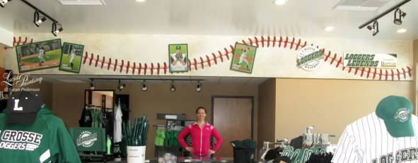 Sarah Pederson stands below the 2017 mural in the La Crosse Loggers Pro Shop.
