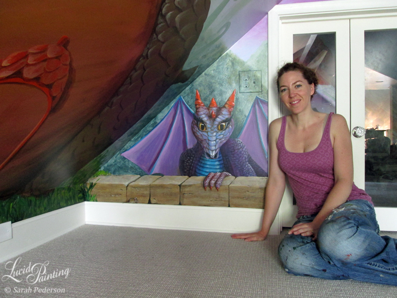 Kid friendly dragon peeking over a faux brick wall with a tiny mouse nearby. The artist sits in front of the door. The dragon has purple scales on her body with blue scales down her chest. She has four orange horns on her head and her three fingers reach over the wall. Her fingers have orange claws. She has long black eyelashes and yellow eyes.