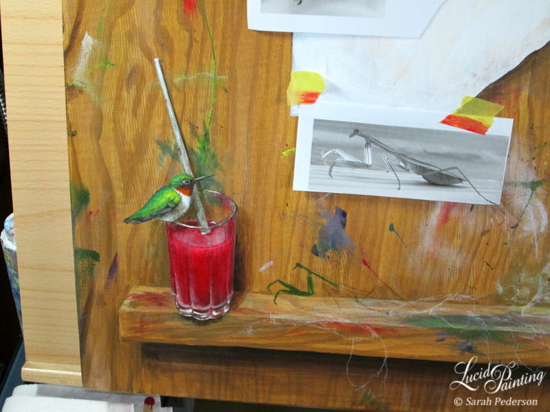 Ruby throated hummingbird is sitting on ledge of glass that is filled with red liquid and has paintbrush resting in the glass. The start of a praying mantis is on the ledge approaching the hummingbird and the outlines of gladiolus flowers is resting on the ledge in front of the praying mantis.