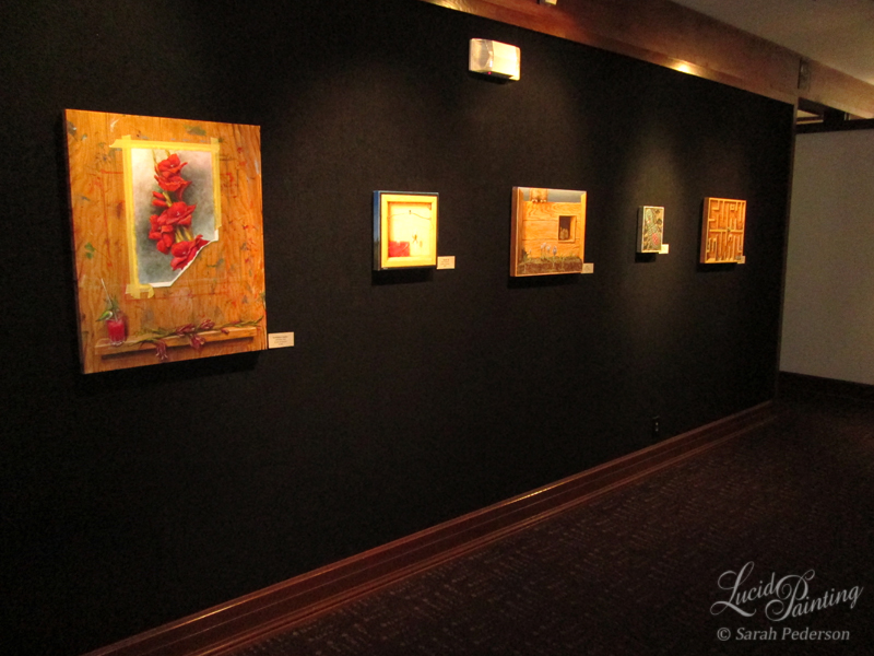 Photograph of five paintings on display at the Pump House. These are all displayed on a black wall with spotlights on each canvas artwork. The largest painting and the one this blog post describes is on the left hand side.