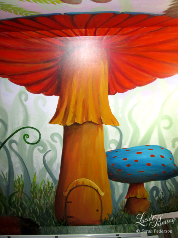 A mushroom with a yellow-orange stem and orange-red underparts and blue cap spans from the floor to the ceiling. The cap of the mushroom crosses onto the opposite wall so you feel like you are below it. A fairy door is at the bottom with a fluted awning to match the mushroom. A smaller mushroom with blue cap and orange spots is behind the large mushroom. Many fantasy curly grasses fill the background and get lighter and lighter in the distance.