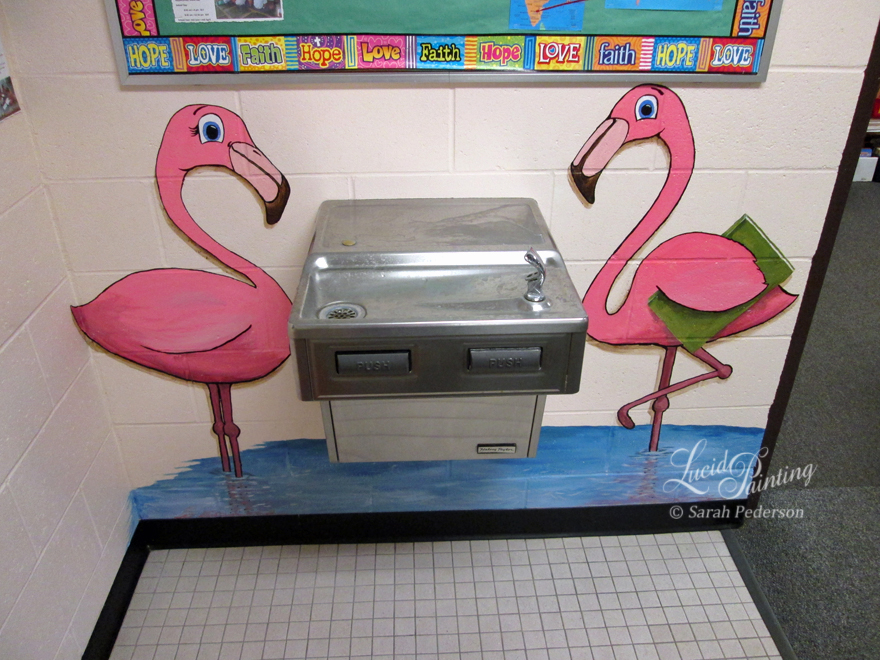 Cartoon flamingos near the water fountain are standing in blue water. The male flamingo is holding a green book.