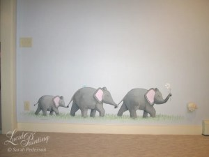 Three elephants march in a grass, holding onto tails of the elephant in front. A baby elephant is in the back. A blue bird sits on the middle elephant and the lead elephant holds a daisy in its trunk. Dots of pastel colors fill the grass to mimic flowers.