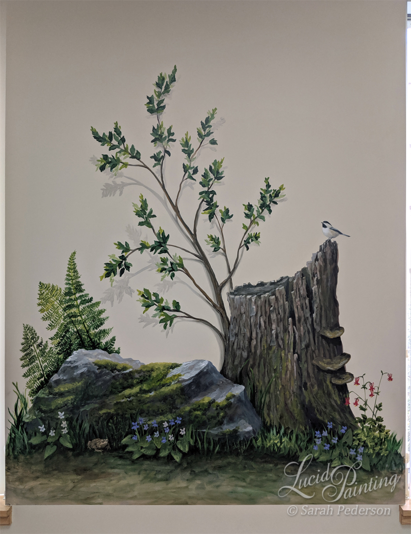 A tree stump appears to be dying but a branch continues to grow upward and outward from the wall, portrayed with shadows. A nearby rock has mosses and ferns with violets in the foreground. A large toad sits at the bottom and a chickadee sits on the stump.