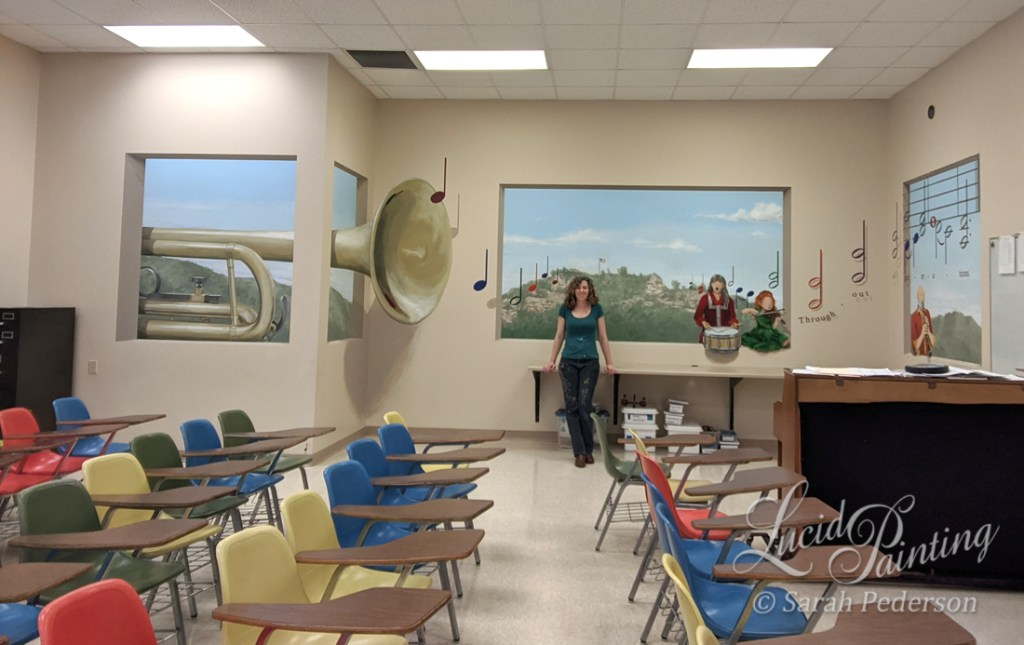 Artist Sarah Pederson stands in front of a trompe l'oeil mural that opens up the walls of a music room in an elementary school. A large trumpet appears to come into the room, spreading musical notes. Granddad Bluff is painted in the distance. A middle aged woman plays a snare drum, a young girl plays a violin, and an elderly man plays a clarinet.