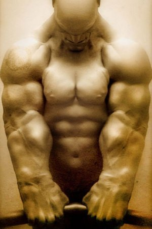 A muscular nude man strains as he bends a metal pipe.