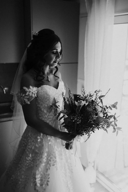 photo mariée au cheveux détachés bouclés long avec son bouquet en noir et blanc
