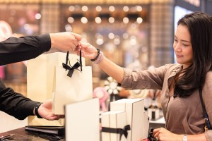 Shop assistant handing shopping bag to female customer