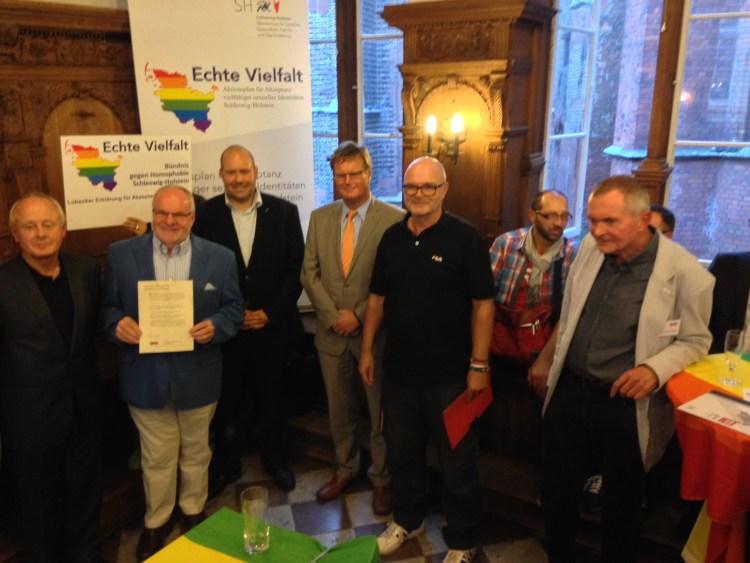 Eine Männerrunde proklamiert ein Bündnis gegen Homophobie. Di einzige Lesbe im Bild hält das Schild.