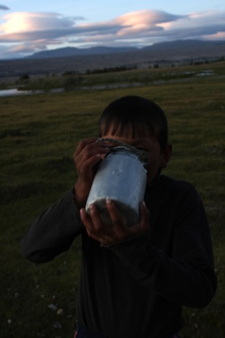 Nomad boy drinking milk beside Khoton lake, Altai Tavan Bogd National Park