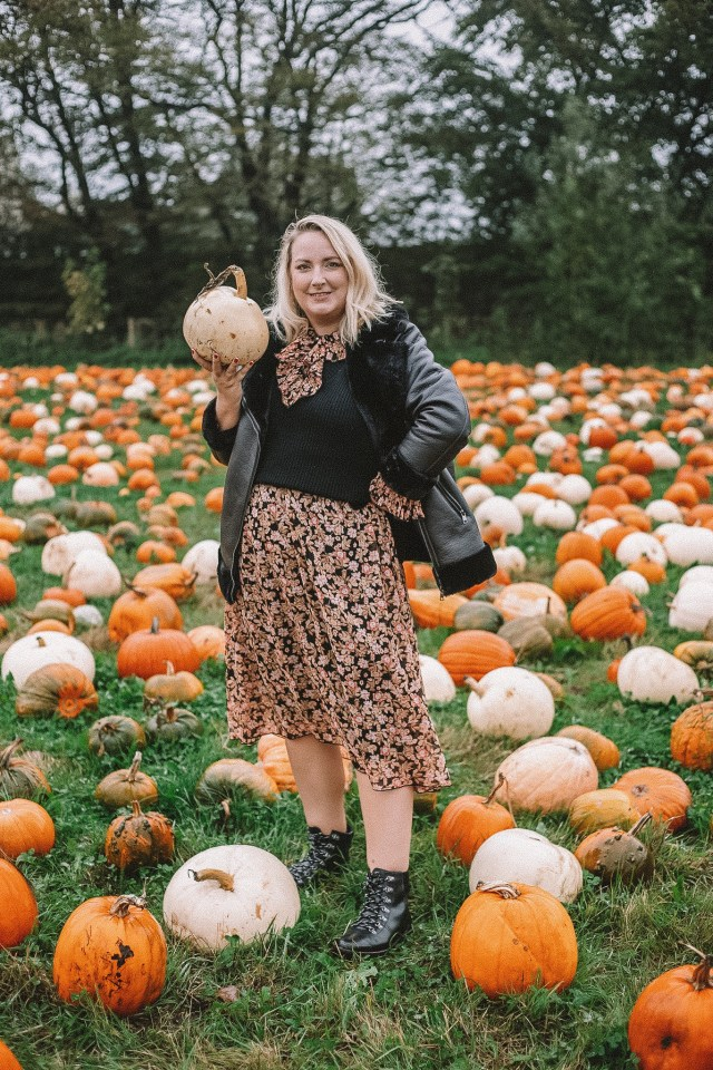 Lucy is stood in a field of pumpkins holding one out to her right