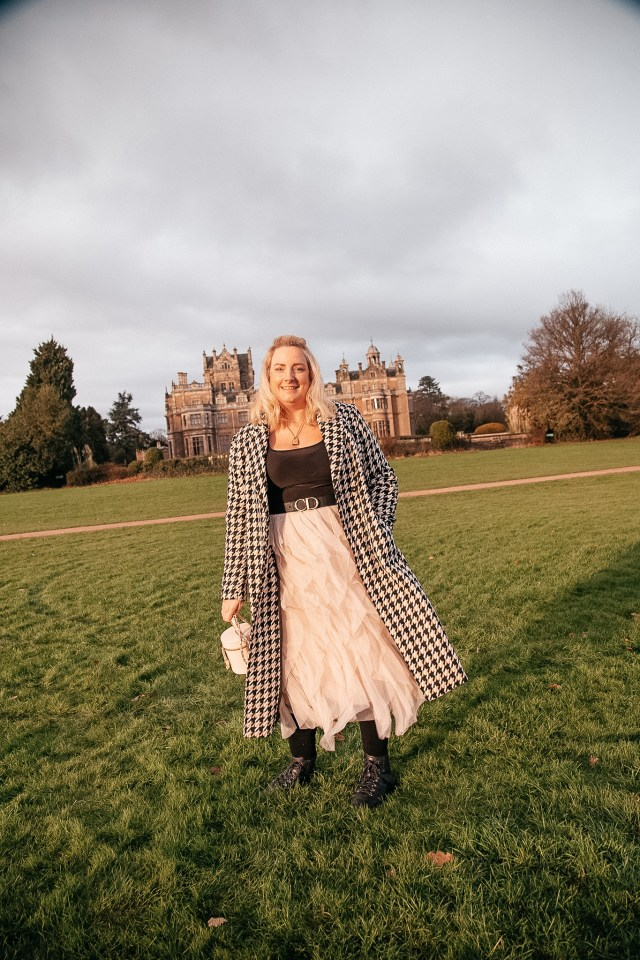 lucy in front of a country house hotel in a mesh skirt, check coat and wearing the plus size dior belt