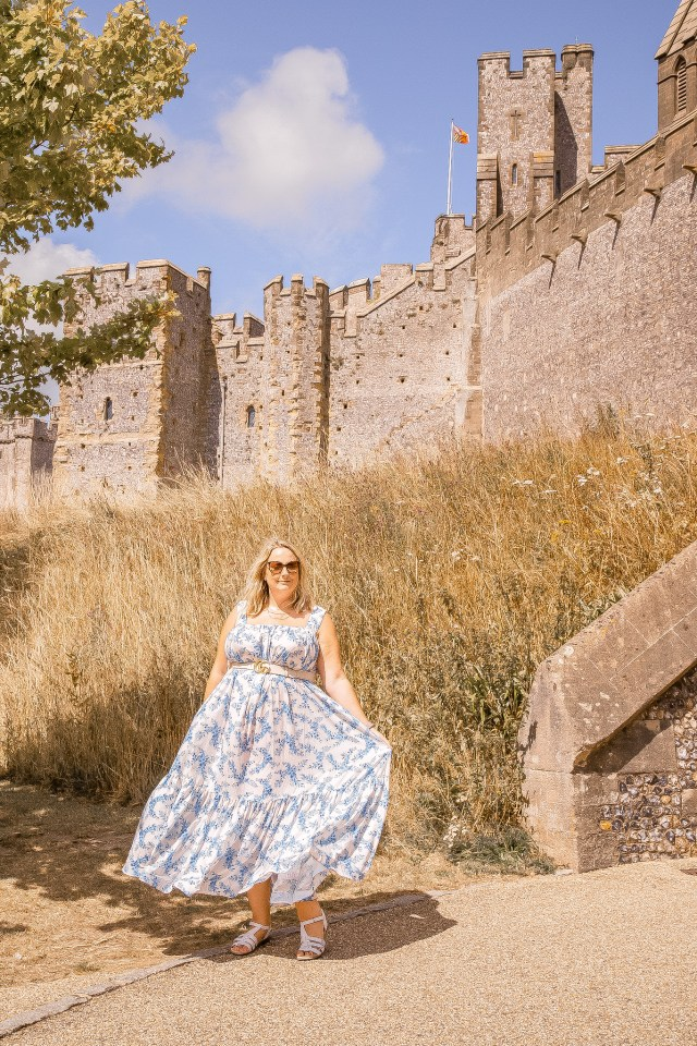 lucy is swishing her blue and white maxi dress and is stood in front of the castle walls