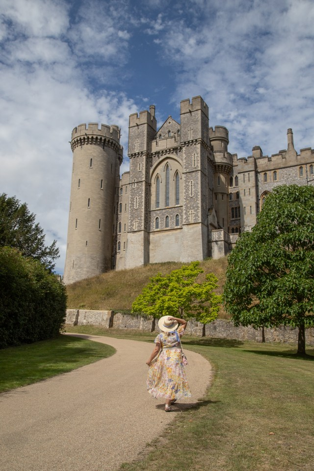 Lucy in her fave neon rose maxi dress and a straw hat looking up to arundel castle