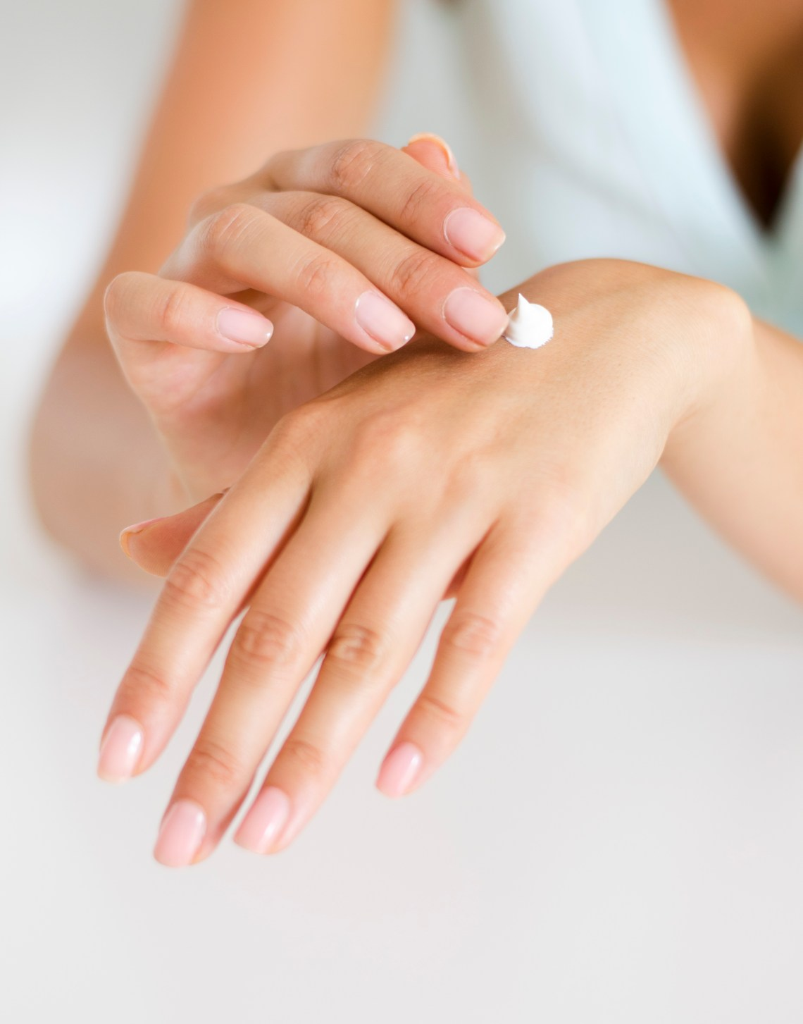 woman rubbing lotion on eczema