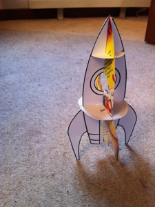 A picture of a rocket was downloaded from the internet, printed four times then stuck onto cardboard, cut out and fixed with a couple of circular 'shelves'.