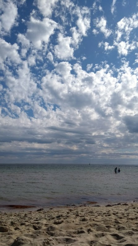 Cielo luminoso pieno di nuvole sopra a mare e spiaggia