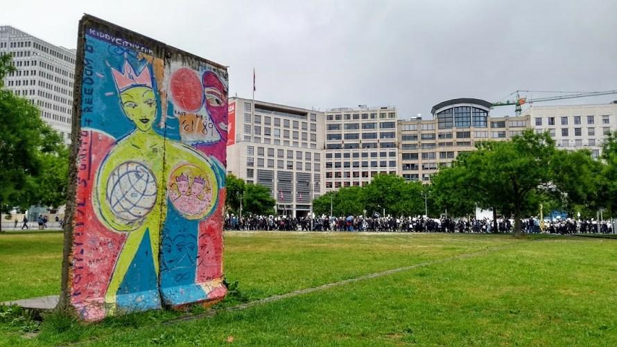 pezzo di muro di berlino con manifestazione sullo sfondo